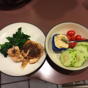 Cucumbers and tomatoes with hummus and salmon over spinach